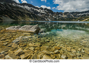 Mountains reflection in alpine lake at sunny day in Tatra...