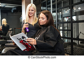 Woman discussing haircut with her hairdresser in the...