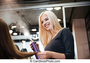 Close-up portrait of a hairdresser with hair spray fixating...