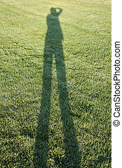 Person casting shadow on grass