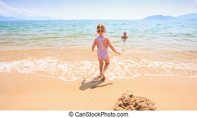 Little Girl Runs in Shallow Water to Mother in Azure Sea -...