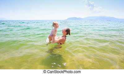 Mother Tosses High up Little Daughter in Azure Sea - closeup...