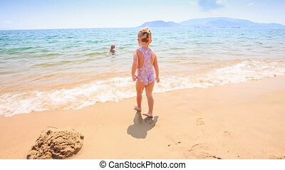 Little Girl Runs to Mother in Shallow Azure Sea Water -...
