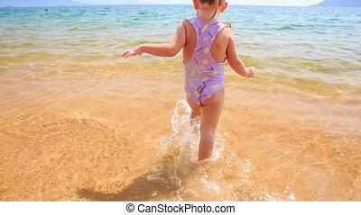 Closeup Blond Little Girl Runs out of Sea to Sand Beach -...
