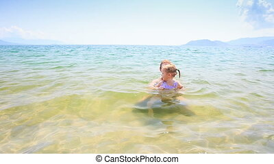 Blond Little Girl Runs out of Sea to Golden Sand Beach -...