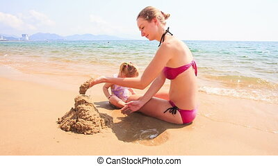 Mother Little Daughter Play with Sand on Beach of Azure Sea