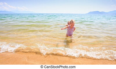 Blond Little Girl Walks out of Sea to Sand Castle on Beach -...