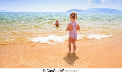 Blond Little Girl Throws Ball to Mother in Shallow Sea -...