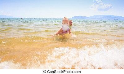 Blond Little Girl Runs with Ball along Sand Beach by Shallow...