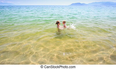 Mother Dandles Little Daughter in Azure Transparent Sea -...
