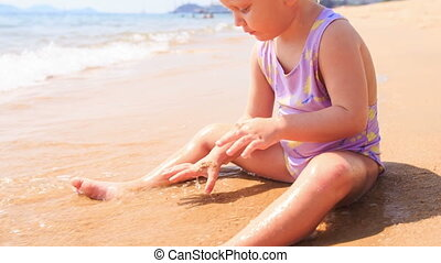 Blond Little Girl Builds Sand Castle on Beach of Azure Sea -...