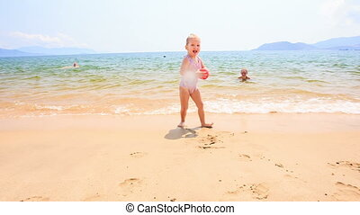 Blond Little Girl Runs with Ball along Sand Beach by Shallow...