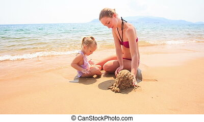 Mother Little Daughter Play with Sand on Beach of Azure Sea...