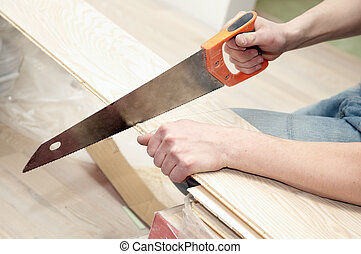 hand saw cutting a board