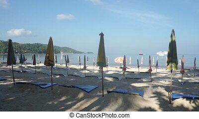 Folded sun umbrellas on Patong beach in the morning Phuket,...