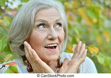 elderly woman in park - Happy elderly woman surprised in a...