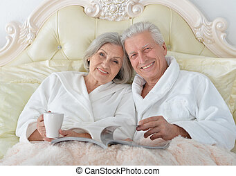 Senior couple in bed with magazine - happy Senior couple...