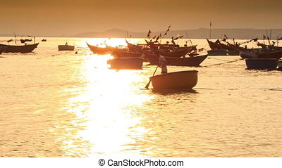 Man Rows Round Fishing Boat among Boats at Sunset in Vietnam...
