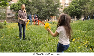 Mother weaves a wreath of dandelions for her daughter -...