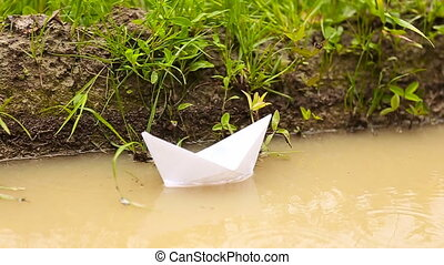 White paper boat floating in a puddle