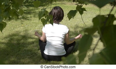Young woman doing yoga outdoors - Girl doing yoga at once...
