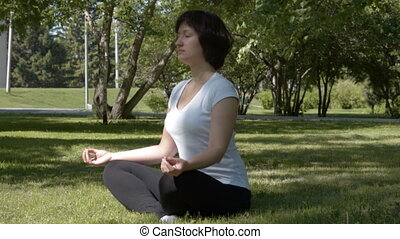Young woman doing yoga in the park - Young woman doing yoga...