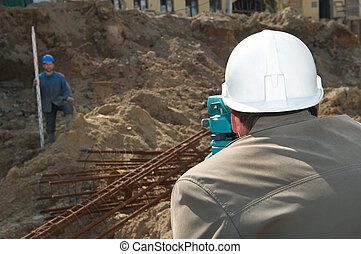 surveyor at construction work - worker surveyor measuring...