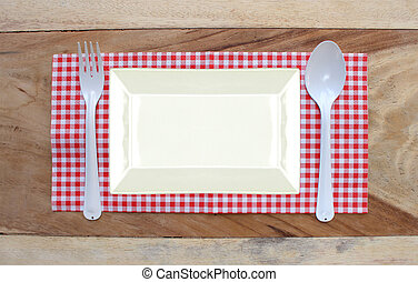 plate on tablecloth and spoon with fork for food serving...