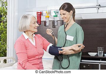 Smiling Nurse Examining Blood Pressure Of Senior Patient