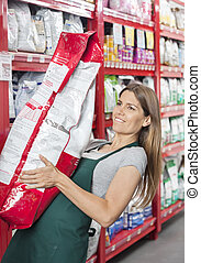 Saleswoman Carrying Heavy Food Package In Pet Store - Mid...