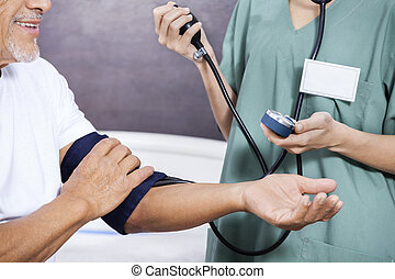 Midsection Of Nurse Checking Blood Pressure Of Senior Patient