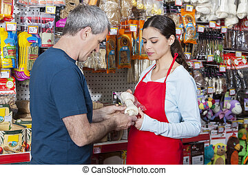 Saleswoman Showing Artificial Bone To Mature Man - Mid adult...