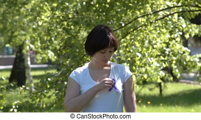Girl wearing purple awareness ribbon - Young woman in white...