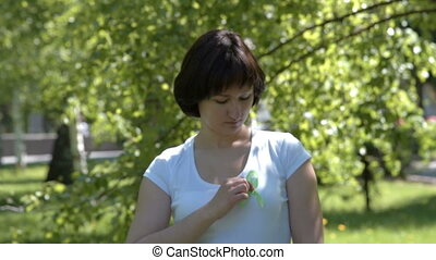 Woman pinning lime green awareness ribbon - Woman pinning...