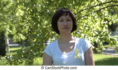 Young woman with yellow awareness ribbon - Young woman in...