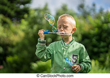 Little boy blows soap bubbles - Little boy playing in the...