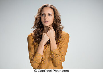 Woman is looking imploring over gray background - The Woman...