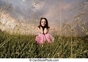Young Woman Wearing A Pink Dress In A Field - A young woman...
