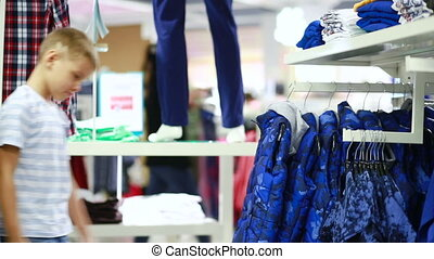 Cute smiling boy stands near clothes and choosing. children...
