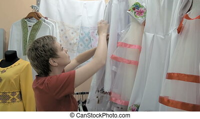 A customer searches for the correct cloth size - A customer...