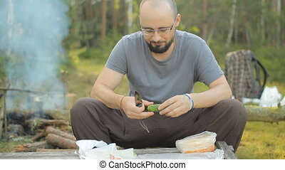 Man sliced cucumber in the camp. Against the backdrop of emits smoke fire and lie tourist stuff
