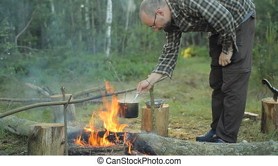Man tries meal with pot. The pot is preparing delicious food in the camp