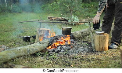 In a pot on the fire boiling water. A man removes scum and...