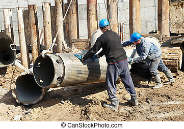 builders with equipment for piling - couple workers...