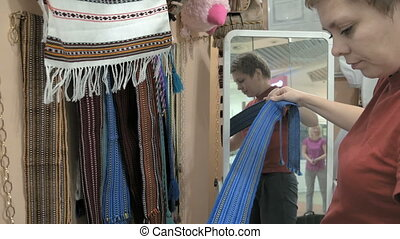 A female customer is trying on a blue waistband - A customer...