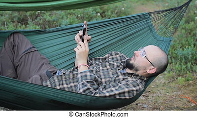 A man in a hammock is calling on the phone. Man in the woods...