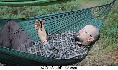 A man in a hammock is video calling on the phone. Man in the...
