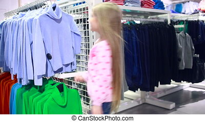 fashionable shop little girl in a clothing store chooses a...