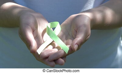 Woman holding lime green awareness ribbon in hands -...