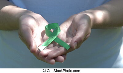 Woman holding green awareness ribbon in hands - Close-up...